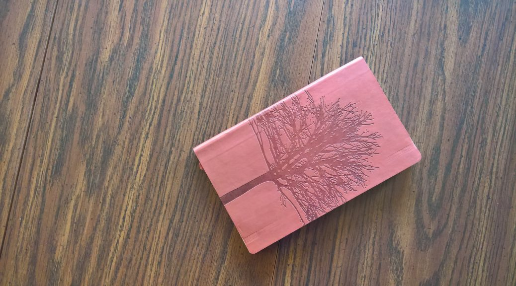 Leather notebook with a tree on the front, on a wooden table